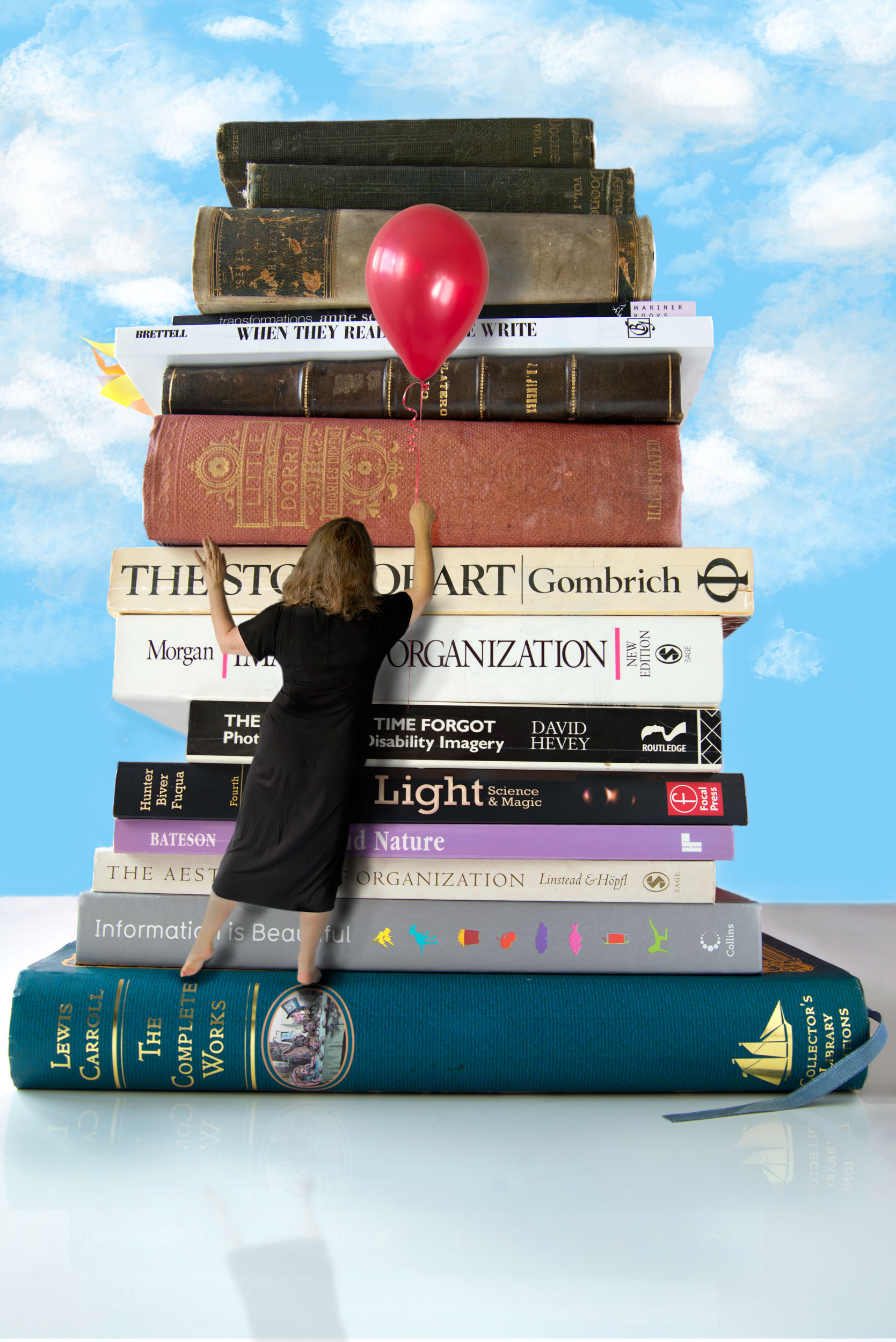 Miniature woman holding a red balloon in front of a tower of books