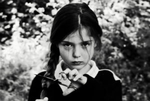 A young girl looks to camera, she is holding scissors across her plait