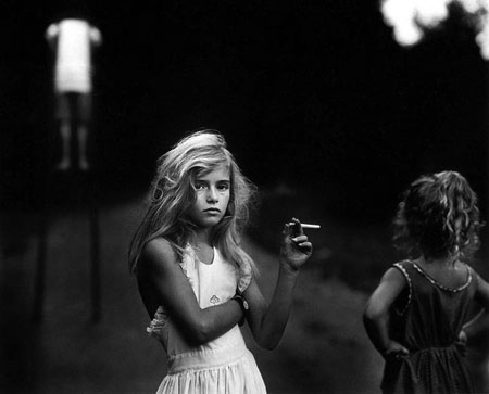 Black and white photograph of two girls one with a candy cigarette