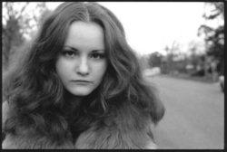 A young women with flowing hair looks direct to camera