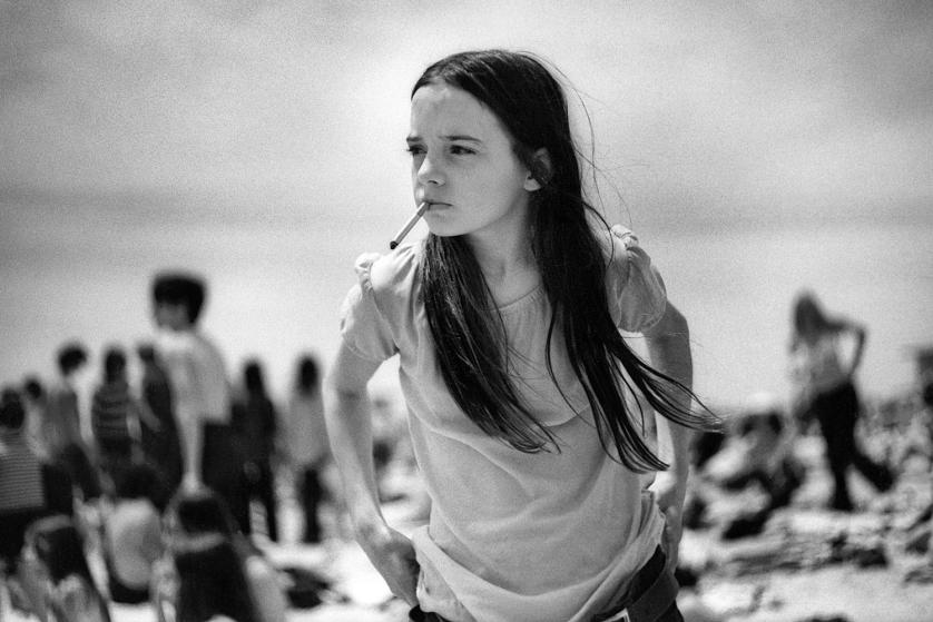 A young girl with a cigarette pulls up her jeans on the beach