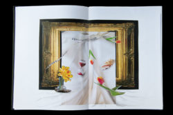 Artists sketchbook with a paper collage of a frame draped in cloth and objects